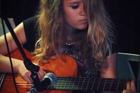 Girl playing accoustic guitar.